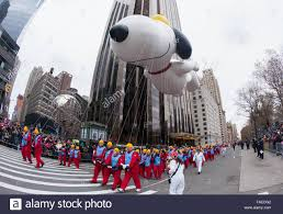 snoopy character balloon floats past crowds during the