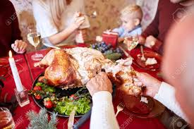 cutting roasted turkey on a table background family enjoying
