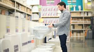 young man shopping in the home improvement store he choosing