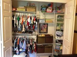 interior small baby closet organizer with sweet clothes in