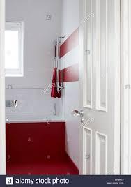 painted bathroom view through open door to red painted bathroom with metallic towel