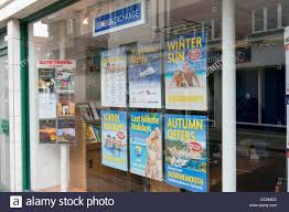 window posters posters in a vacation travel agents window display stock photo