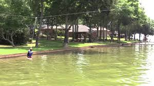 homemade zip line over water using an umbrella stand full of sand