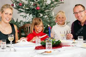 family eating a traditional christmas dinner in front