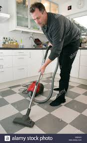 middle aged a vacuum cleaner on the kitchen tiled floor