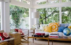colorful cushions on white couch front globe on wood table inside