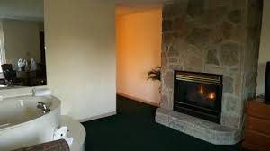 room off from bedroom with jacuzzi fireplace tv couch and table