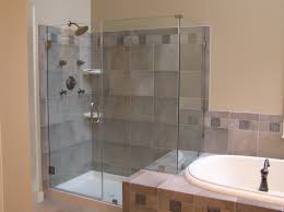 white bathtub and small glass shower stalls with grey tile wall