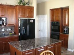 kitchen white galley kitchen with black appliances fireplace