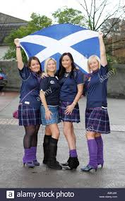 four scottish girls in tartan kilts and saltire flag prepare to
