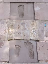 glittering shards make mosaic cement foot prints and hand prints