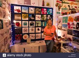a stall holder specializing in unique clocks smiles for her