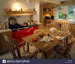red aga oven in traditional country kitchen with wooden dining