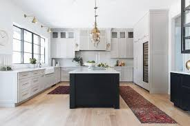 kitchen with black island and white cabinets black island with light gray perimeter cabinets