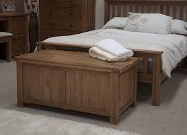 blanket storage box as bench seat beside wooden bed with white bed