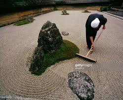 monk raking rock garden of ryoanji temple japan stock photo