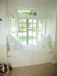 monochromatic white room with bay window window seat french