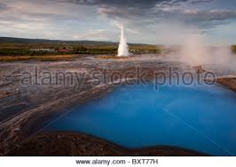 iceland geysir rising sun lights blue thermal pool and tower of
