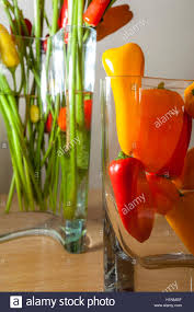 large arrangement of flowers in a glass vase that includes stock
