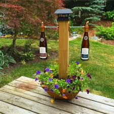 dual tiki torch holder with a solar light on top and planter on