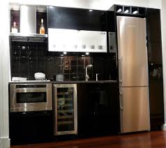 black cabinet and silver steel beside high silver fridge placed on