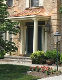 copper portico with tapered columns and stone patio land art