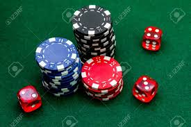 poker table top and chips poker chips and dice on a green gaming table top view close up stock