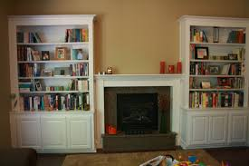 white wooden shelf cabinet flanking cement mantel fireplace most