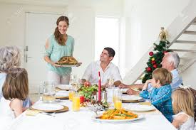 mother serving christmas meal to family at dining table stock