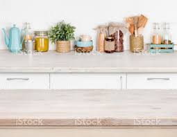 wooden kitchen table over blurred furniture shelf with food