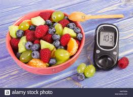 fresh fruit salad and glucose meter with result of measurement