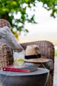 Wicker Armchair Outdoor Refreshing Drink On Book On Side Table Next To Wicker Armchair