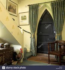 green curtains on gothic style door in nineties hall with a rustic