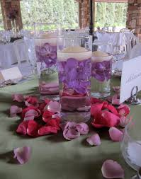 candle and red rose arrangement on grey table cloth for wedding