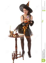 in halloween witch costume prepares a potion stock images