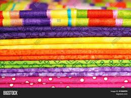 textile background macro of folded cotton fabrics in bright