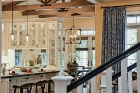mixing glass pendant lights and a rustic caged chandelier creates