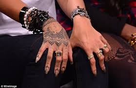rihanna admires the new tattoo on her right wrist after staying up