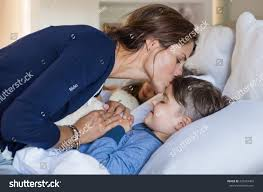 girls kissing in bed mother giving good night kiss sleeping stock photo 425022403