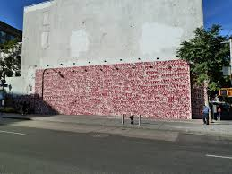 wall in new york covered with hundreds of red tags public delivery barry mcgee mural on houston and bowery new york 2010