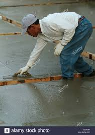 workman leveling wet concrete with a darby during construction of