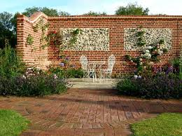 pair of windows in flint wall with brick quoins garden