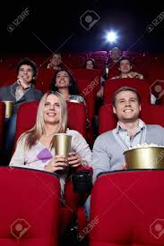 smiling people are watching movies in cinema stock photo picture