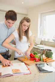 livre cuisine homme femme coupant des poivrons avec le livre de cuisine de lecture de l