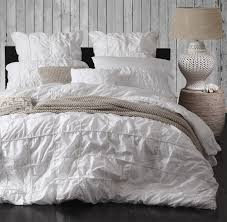 bedroom white ruffle comforter with desk lamp and side table for
