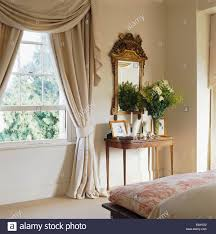 beige silk swagged tailed pelmet and curtains on window in country
