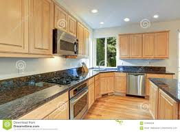oak kitchen cabinets with stainless steel appliances sun filled gourmet kitchen with wooden cabinetry stock photo