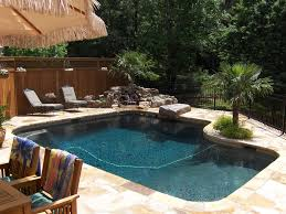 tropical swimming pool with exterior stone floors by arnold