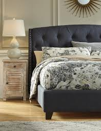 king upholstered bed in dark gray with tufting and nailhead trim