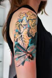 dragonfly sitting on leaves on half sleeve